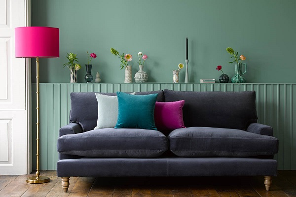 dark velvet sofa against green wall with vases of flowers behind