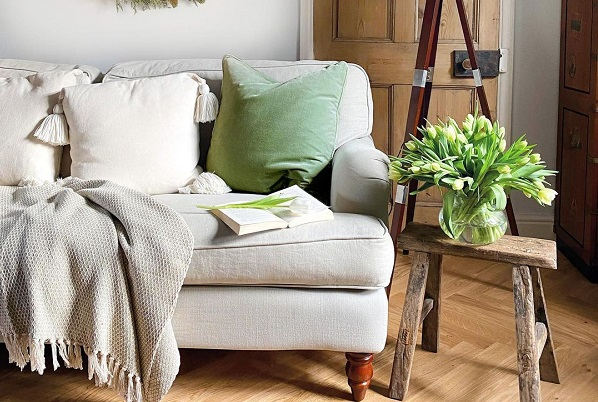 neutral sofa, with spring styling featuring green cushions, a spring wreath and fresh tulipsneutral sofa, with spring styling featuring green cushions, a spring wreath and fresh tulips