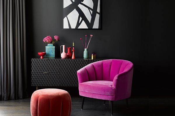 pink velvet cocktail chair in front of abstract art